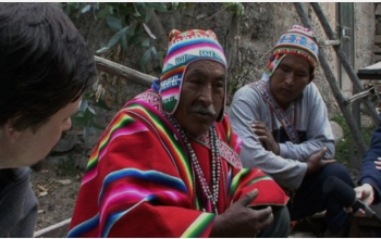 Photo shows indigenous Bolivian men being interviewed by linguists.